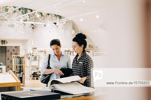 Verkäuferin hilft weiblichen Kunden bei der Auswahl von Tapetenmustern im Geschäft