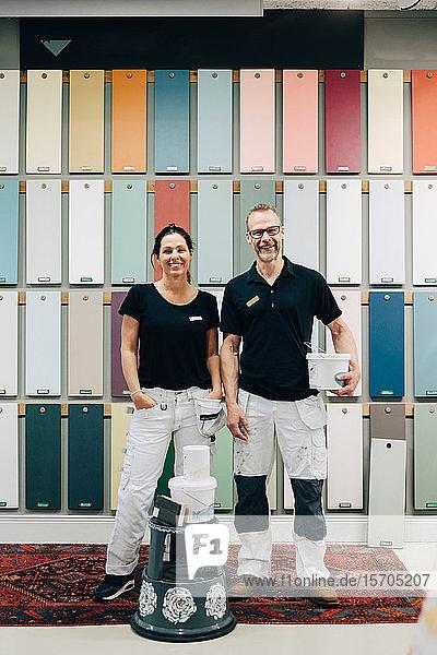 Porträt in voller Länge von lächelnden Kollegen  die vor einer mehrfarbigen Wand im Laden stehen