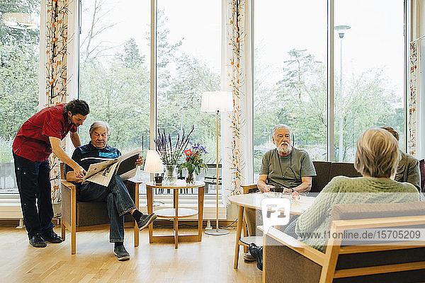 Krankenpfleger steht neben einem älteren Mann  der Zeitung liest  während sich Freunde im Ruhestand im Pflegeheim unterhalten