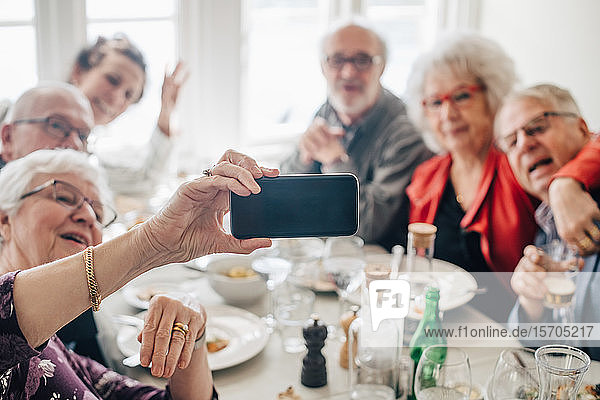 woman clicking photograph of Senior friends through smart phone while sitting in restaurant