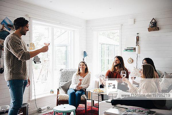 Lächelnder Mann hält Rede  während er während einer Party zu Hause mit Wein auf Freunde anstößt