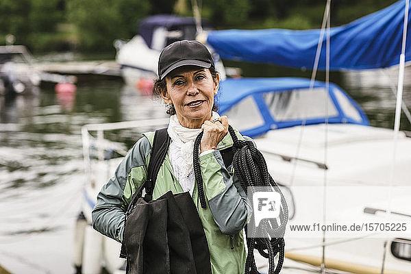 Porträt einer selbstbewussten Ausbilderin  die während des Bootsführerkurses Seil und Schwimmwesten gegen die Yacht hält