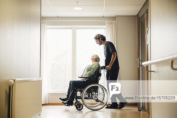 Seitenansicht in voller Länge eines Pflegers  der eine behinderte ältere Frau im Rollstuhl in einer Gasse im Altenheim schiebt