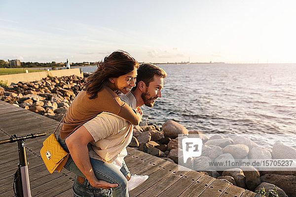 Mann nimmt glückliche Freundin huckepack  während er im Urlaub auf der Strandpromenade genießt
