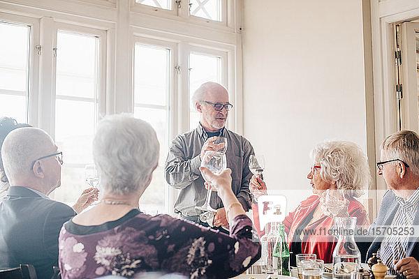 Ältere Freunde beim Weinglas-Toast im Restaurant