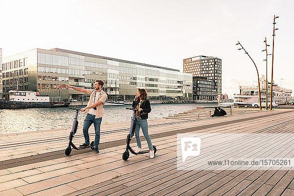Ein Paar erkundet die Stadt während einer Fahrt auf elektrischen Rollern an der Uferpromenade