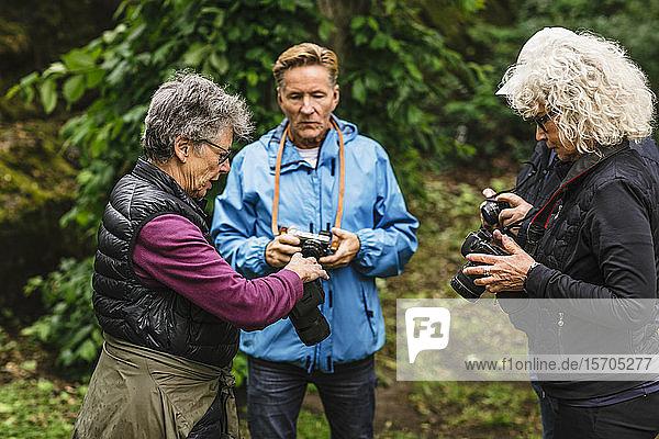 Ältere Frauen und Männer  die die Kamera während des Fotokurses benutzen