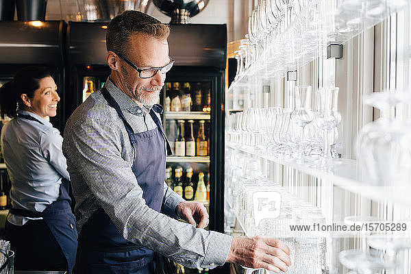 Reifer Mann arrangiert Weingläser  während die Kellnerin im Hintergrund im Restaurant sitzt