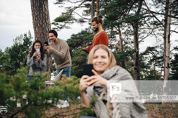 Freundinnen und Freunde benutzen Smartphones  während sie sich im Wald ausruhen