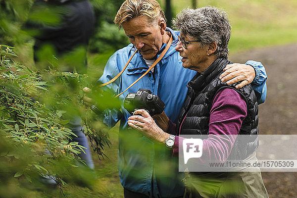Ältere Frau zeigt einem Freund während eines Fotokurses eine Kamera