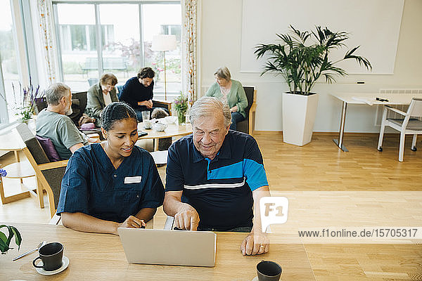 Young female nurse assisting senior man using laptop at dining table in retirement home