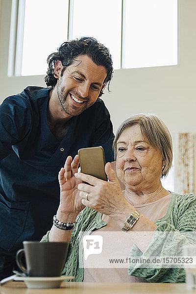 Lächelnder männlicher Betreuer unterstützt ältere Frau bei der Nutzung eines Smartphones im Pflegeheim