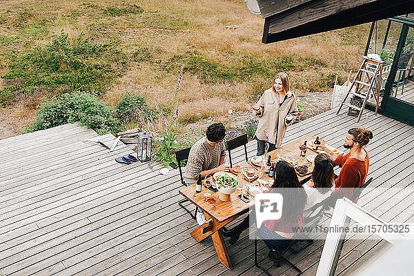 Schrägansicht einer Frau  die sich mit Freunden unterhält  während sie auf der Terrasse zu Abend isst