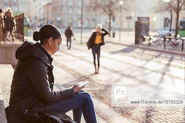 Teenager-Mädchen benutzt Mobiltelefon  während sie auf Stufen in der Stadt sitzt