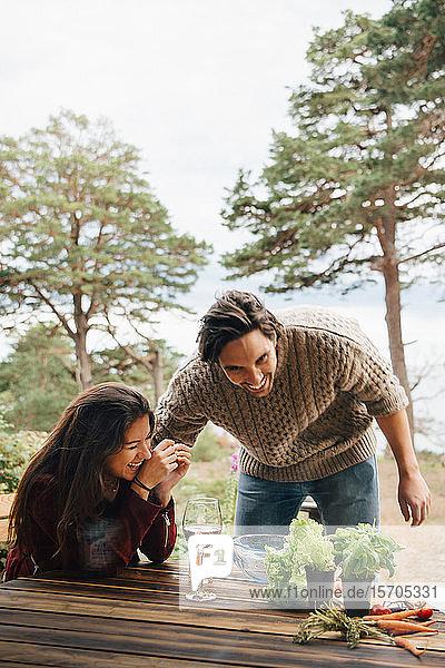 Mann und Frau im mittleren Erwachsenenalter haben Spaß bei der Zubereitung von Mahlzeiten am Tisch im Innenhof