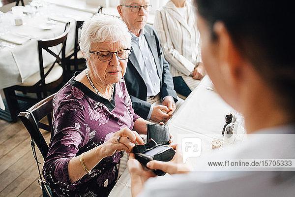 Schrägaufnahme eines Eigentümers  der ein Kreditkartenlesegerät hält  während eine ältere Frau im Restaurant bezahlt