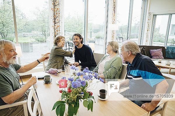 Lächelnder Mann sitzt inmitten älterer Menschen  die am Esstisch gegen das Fenster im Pflegeheim sitzen