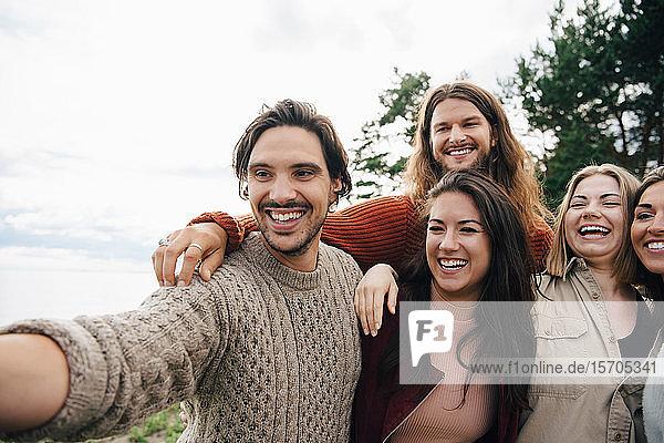 Fröhliche männliche und weibliche Freunde  die sich im Freien vergnügen