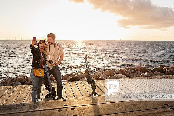 Frau  die mit ihrem Freund Selbsthilfe nimmt  während sie an elektrischen Rollern auf der Promenade gegen das Meer steht