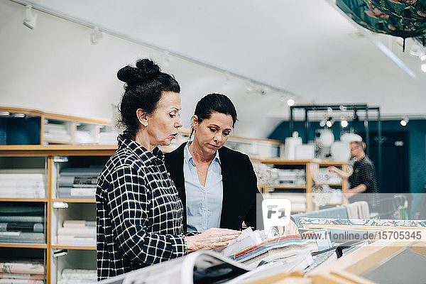 Senior saleswoman showing wallpaper sample to customer in store