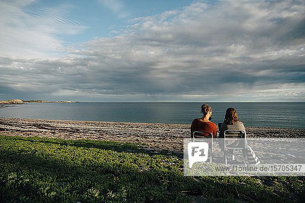 Rückansicht von Freunden  die auf Stühlen am Meeresufer vor bewölktem Himmel sitzen