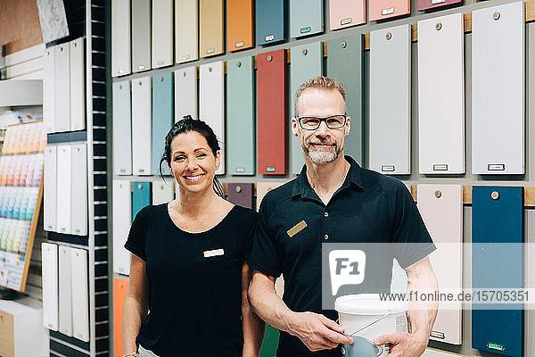 Porträt von lächelnden Mitarbeitern  die vor einer mehrfarbigen Wand im Laden stehen