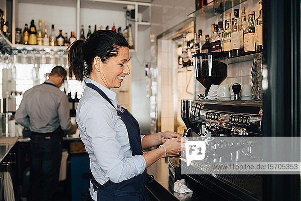 Lächelnder Barista mit Kaffeemaschine im Restaurant