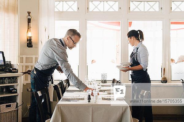 Männliche und weibliche Mitarbeiter bei der Tischordnung im Restaurant, Männliche und weibliche Mitarbeiter bei der Tischordnung im Restaurant