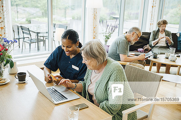 Smiling female healthcare worker assisting senior woman doing online shopping with credit card and laptop in nursing hom