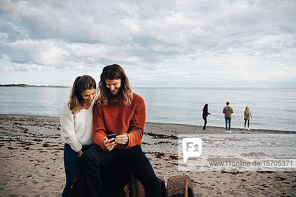 Ehepaar  das am Strand am Meer sitzend auf sein Handy schaut