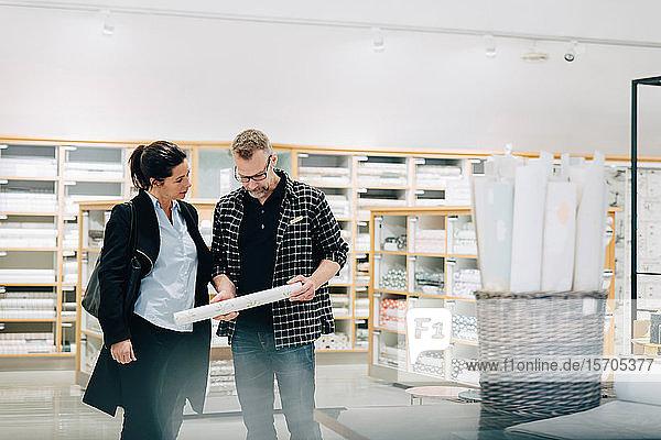 Verkäufer zeigt weiblichen Kunden im Geschäft Tapete