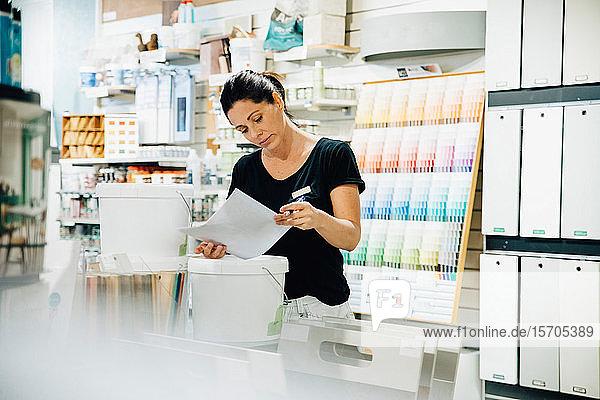 Weibliche Angestellte liest Dokument im Baumarkt