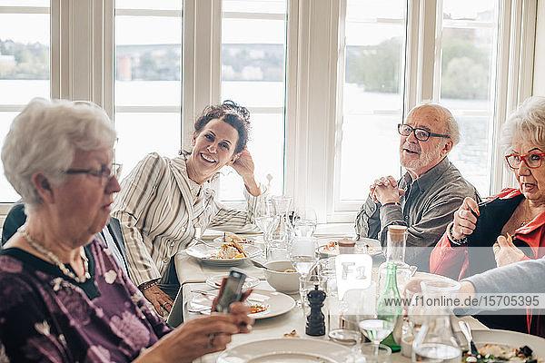 Ältere Freunde unterhalten sich  während sie im Restaurant sitzen