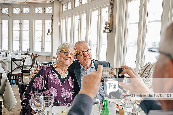 male friend clicking photograph of Senior couple in restaurant