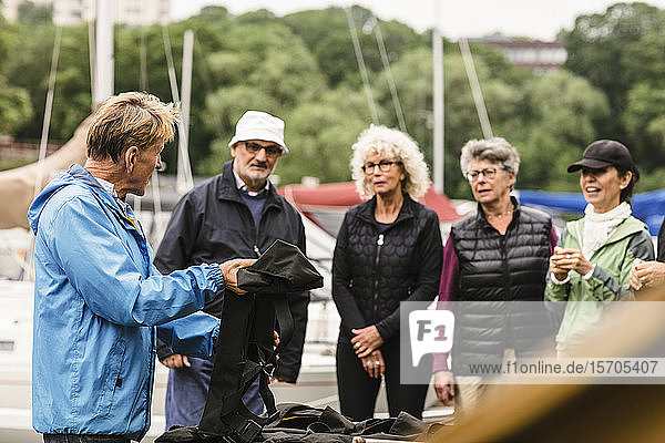 Männlicher Ausbilder erklärt älteren Männern und Frauen während des Bootsführerkurses die Schwimmweste