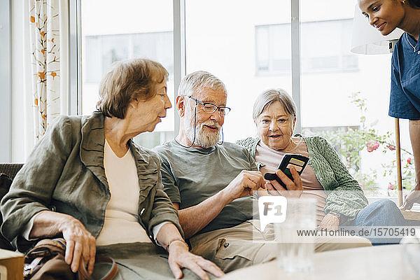 Älterer Mann benutzt Smartphone  während er inmitten von Frauen im Altersheim sitzt