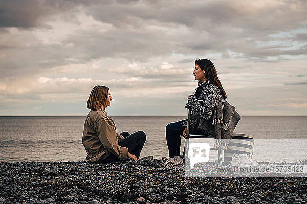 Freundinnen unterhalten sich  während sie am Strand vor bewölktem Himmel sitzen
