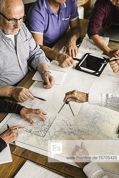 Hochwinkelansicht von älteren Männern und Frauen mit Karte am Tisch während des Navigationskurses