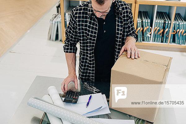 Hochwinkelansicht des Verkäufers mit dem Taschenrechner durch Karton im Geschäft