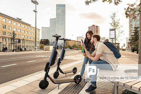 Mann zeigt seiner Freundin ein Smartphone  während er in der Stadt an einem Elektroroller sitzt