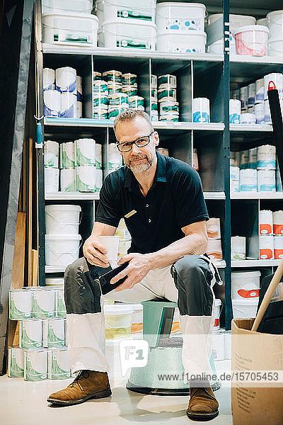 Ganzflächiges Porträt eines Verkäufers  der auf einem Hocker im Lagerraum sitzt