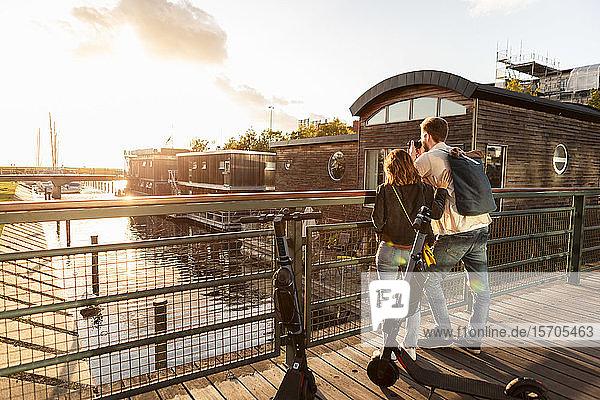 Paar mit Elektroschubroller fotografiert Fluss,  während es auf einer Brücke in der Stadt steht