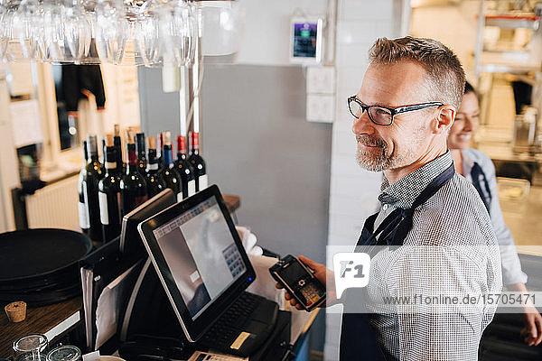 Lächelnder Mann benutzt Computer  während er im Restaurant ein Kreditkartenlesegerät in der Hand hält