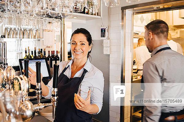 Männlicher und weiblicher Besitzer im Restaurant stehend