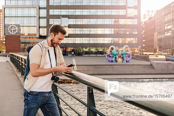 Mittelgroßer erwachsener Mann benutzt Smartphone  während er in der Stadt am Geländer steht