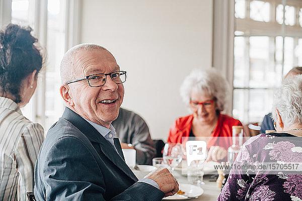 Porträt eines älteren Mannes  der lächelnd neben Freunden im Restaurant sitzt