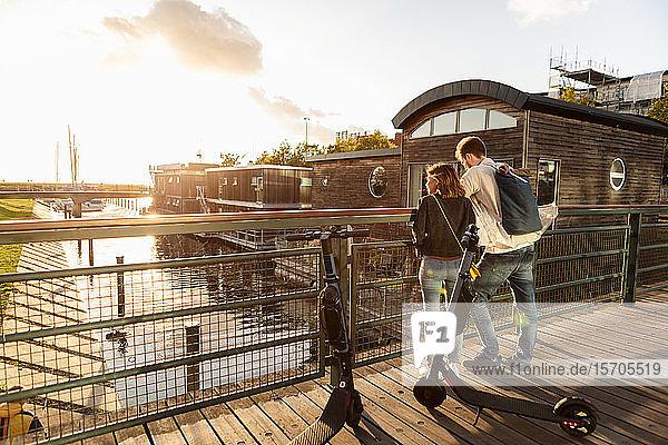 Paar mit elektrischen Schubrollern steht auf Brücke über Fluss in Stadt gegen Himmel