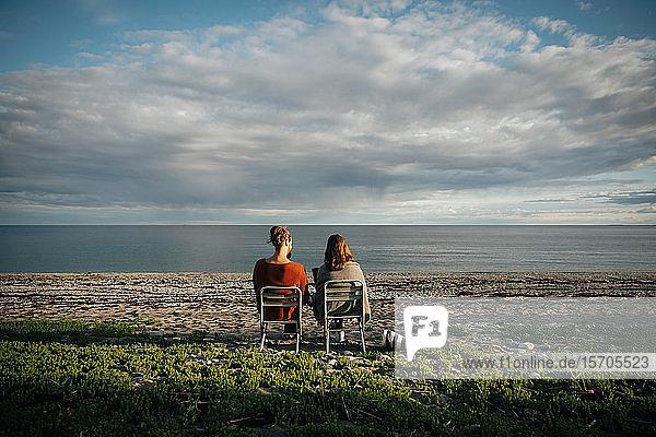 Rückansicht von Freunden  die auf einem Stuhl am Strand vor bewölktem Himmel sitzen