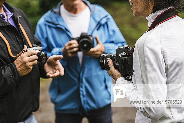 Weibliche Ausbilderin erklärt älteren Männern während eines Fotokurses