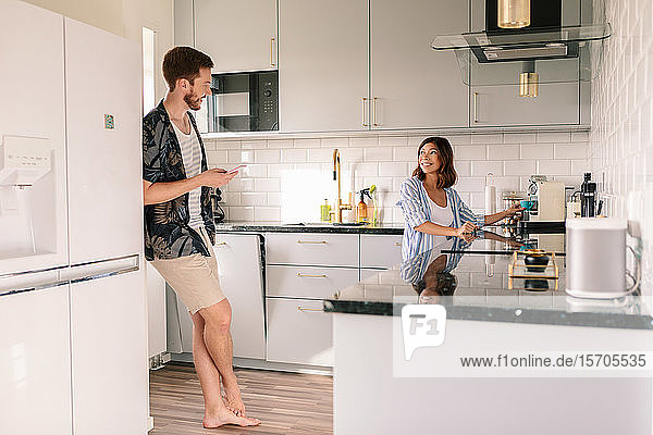Smiling woman making coffee while looking at man using phone in kitchen